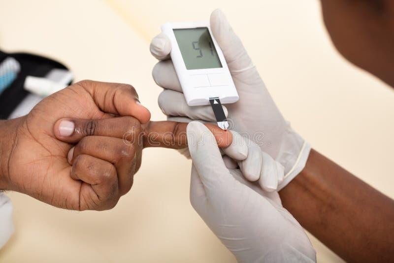 Checking Patient医生的与Glucometer的血糖水平 免版税库存照片