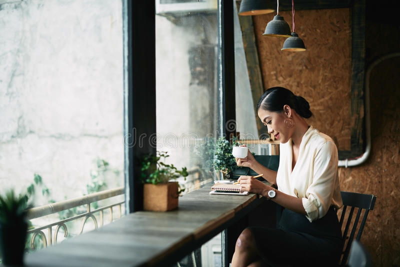 Checking planner. Pretty smiling business lady drinking coffee and checking her daily planner stock photo