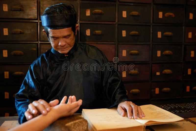 Checking pulse. Chinese medicine practitioner checking pulse of female patient royalty free stock photography