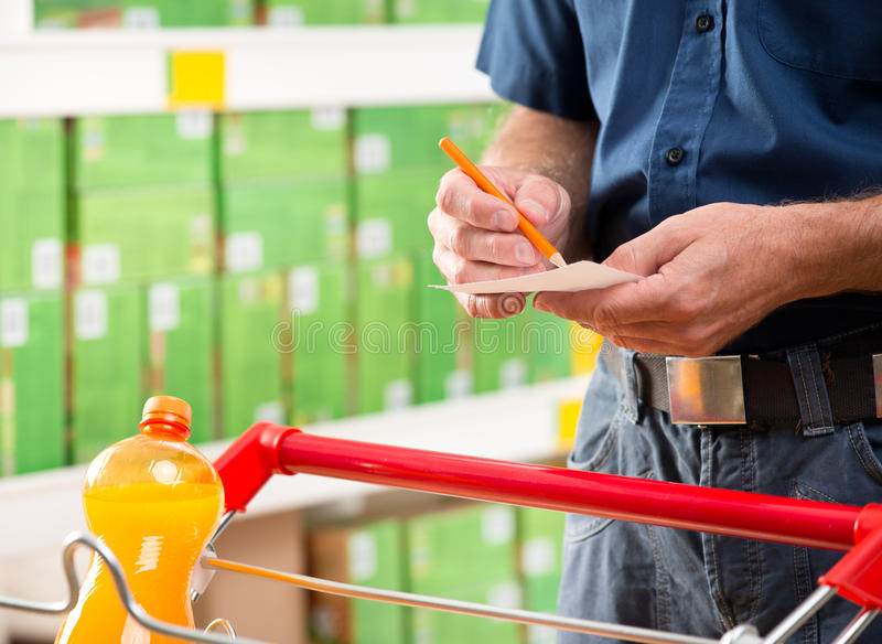 Checking shopping list. Man with trolley checking shopping list at supermarket royalty free stock images
