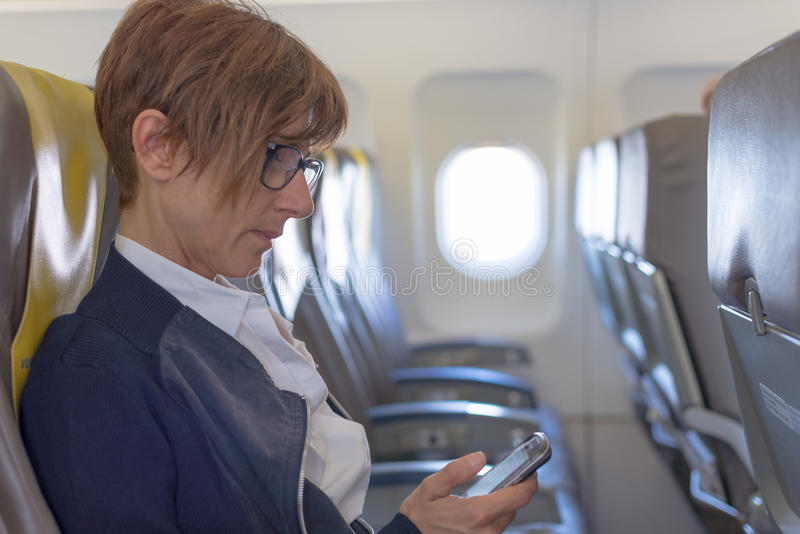 Checking smart phone in the airplane. Businesswoman sending message with mobile phone while sitting in the aircraft before departure. Concept of people sharing royalty free stock image