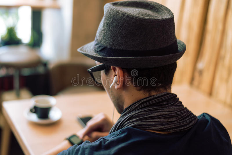Checking smartwatch. Young stylish and fashionable man checking his smartwatch in cafe bar. High angle shot. Selective focus. Toned image royalty free stock photo