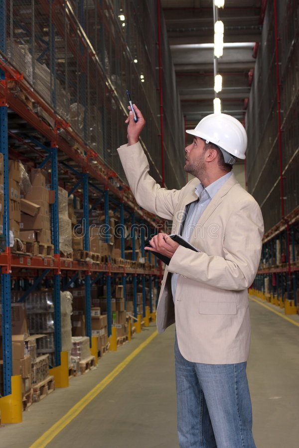 Checking Stocks. A supervisor counting products stacked on the shelves in a factory storeroom royalty free stock image