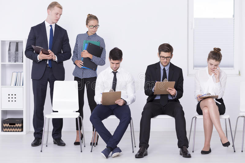 Checking their answers. Shot of a job candidates doing a pre-assessment test while supervisors are looking over their shoulders stock image