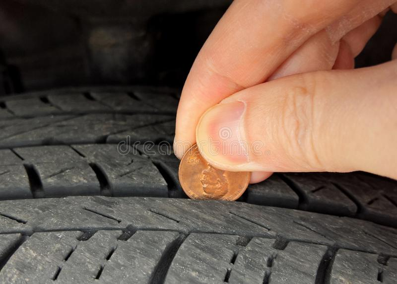 Checking tire tread depth/wear with a penny royalty free stock images