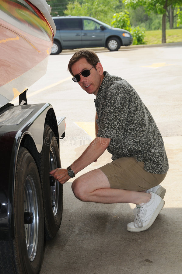 Checking Tires. Man checking tire pressure and tightening the lug nuts on his wheels at a service station stock photography