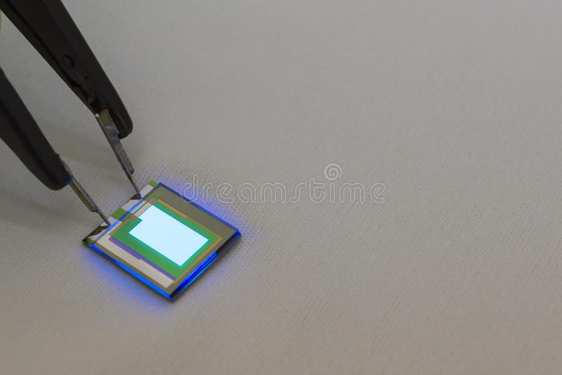 Checking turn on small oled display of blue color with a probe station. Checking turn on small tiny oled display of blue color with a probe station.Grey royalty free stock photo