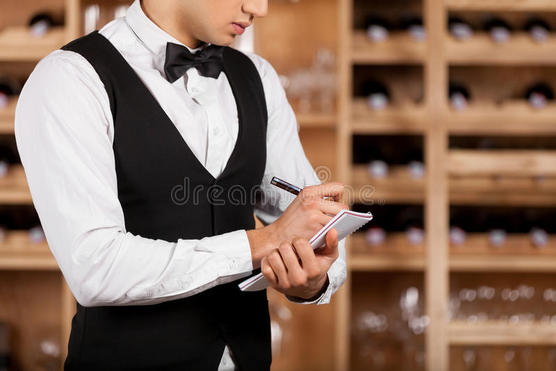 Checking wine list. Cropped image of young sommelier writing something at his note pad while standing in front of shelf with wine bottles stock photo