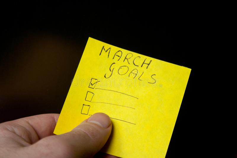 Checklist with march goals on balck background. Yellow note paper in human hand. Checklist with march goals on balck background royalty free stock images