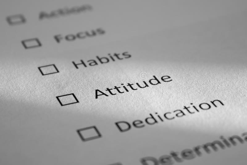 Checklist on a white sheet of paper with points Action, Focus, Habits, Attitude, Dedication. The inscription Attitude is. Highlighted by a beam of light and is royalty free stock photos