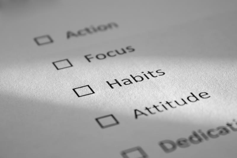 Checklist on a white sheet of paper with points Action, Focus, Habits, Attitude. The inscription Habits is highlighted by a beam. Of light and is in focus royalty free stock photo