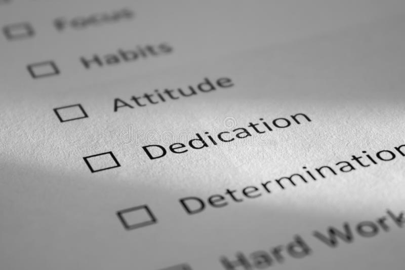 Checklist on a white sheet of paper with points Focus, Habits, Attitude, Dedication, Determination. The inscription Dedication is. Highlighted by a beam of stock photos