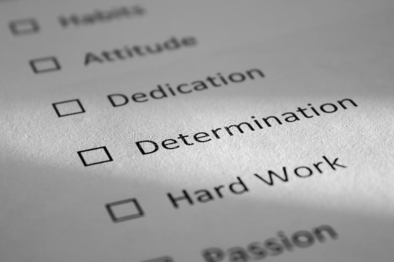 Checklist on a white sheet of paper with points Habits, Attitude, Dedication, Determination, Hard Work. The inscription. Determination is highlighted by a beam stock photography