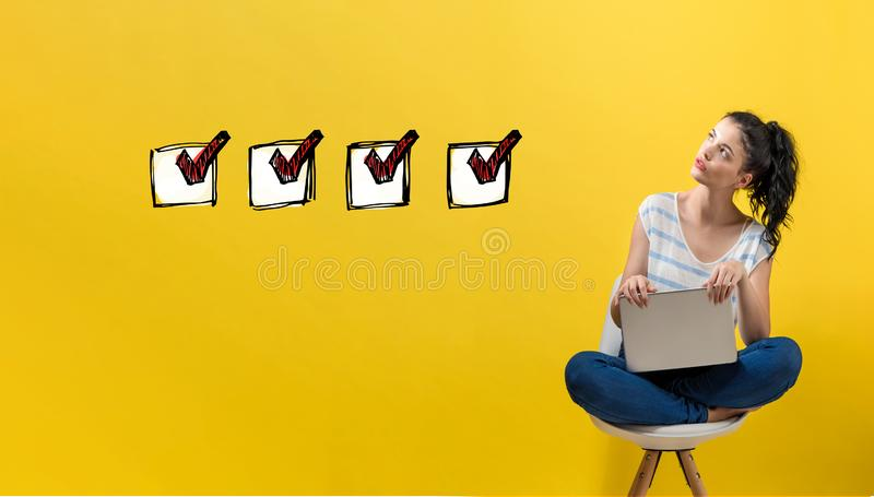Checklist with woman using a laptop. Checklist with young woman using a laptop computer royalty free stock photo