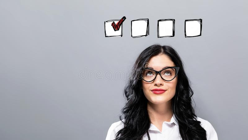 Checklist with young businesswoman. In a thoughtful face royalty free stock image