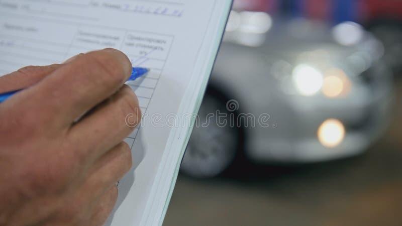 Checkmarks - pracownik robi sprawdzać samochód rozdziela w garażu warsztacie fotografia royalty free