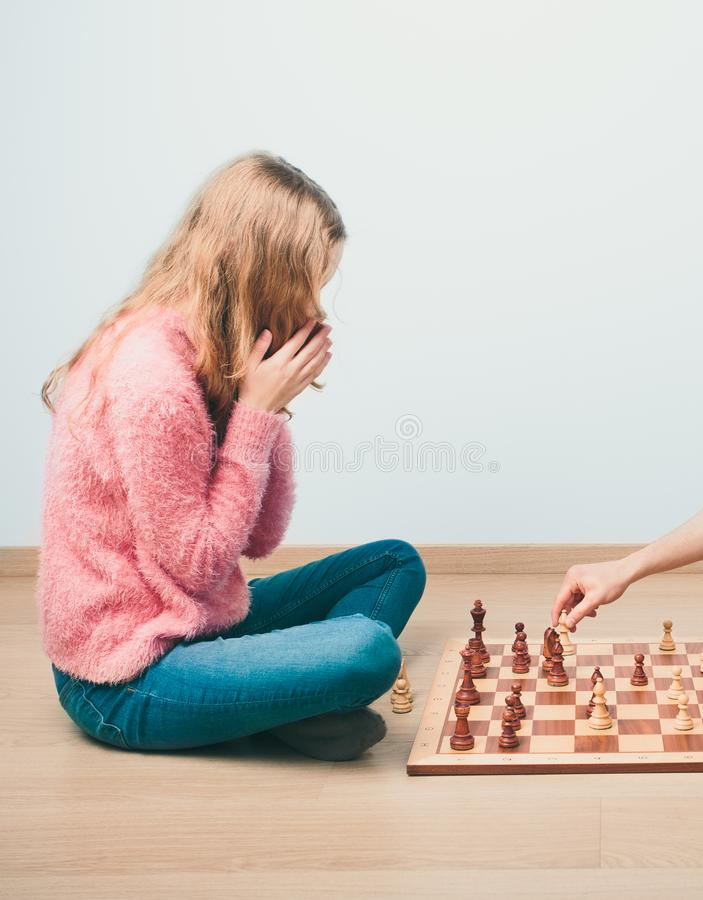 Checkmate. Girl is surprised by last move her rival in chess game royalty free stock image