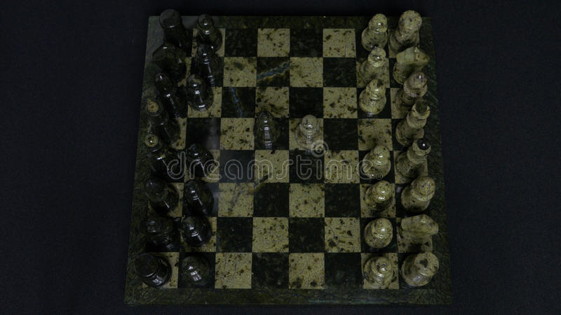 Checkmate. Start Of A Chess Game,the Figures Are Lined Up And A Person Makes The First Move. Hand moving a knight chess. Piece on chessboard. Man`s hands play royalty free stock photos