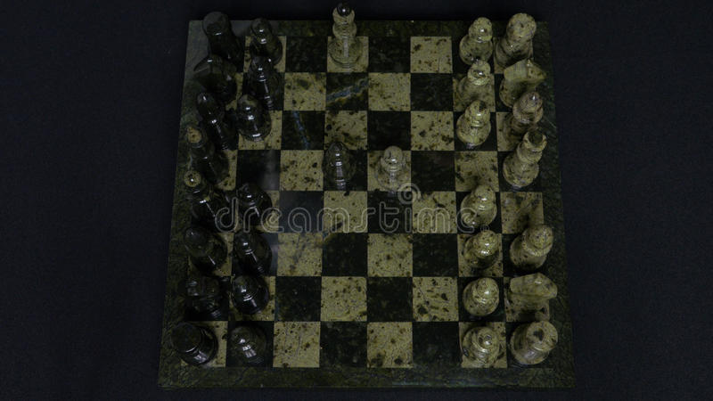 Checkmate. Start Of A Chess Game,the Figures Are Lined Up And A Person Makes The First Move. Hand moving a knight chess. Piece on chessboard. Man`s hands play stock photography
