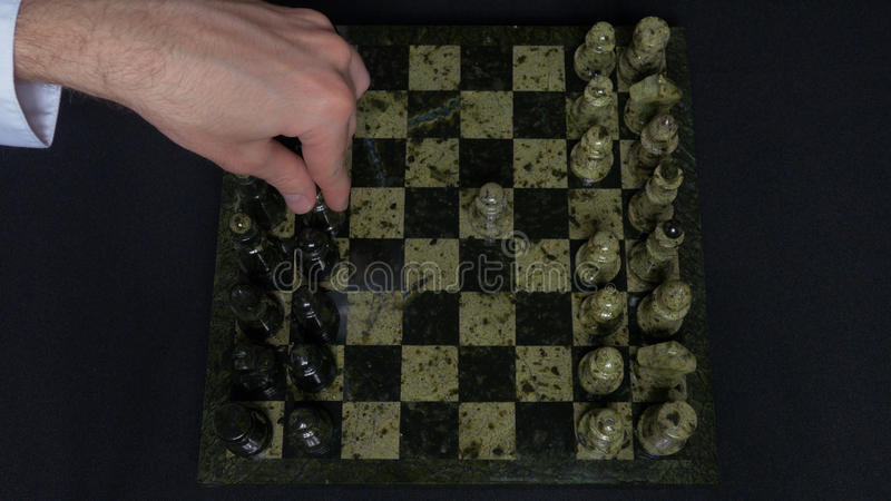 Checkmate. Start Of A Chess Game,the Figures Are Lined Up And A Person Makes The First Move. Hand moving a knight chess. Piece on chessboard. Man`s hands play stock image