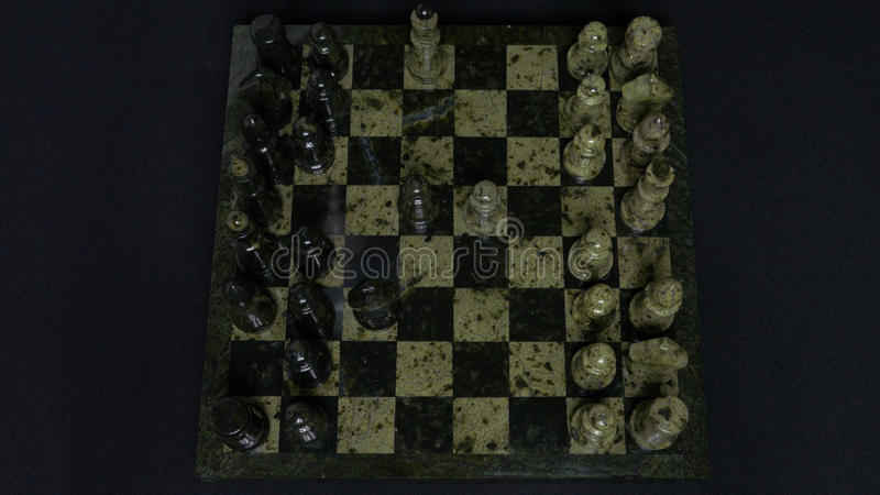 Checkmate. Start Of A Chess Game,the Figures Are Lined Up And A Person Makes The First Move. Hand moving a knight chess. Piece on chessboard. Man`s hands play royalty free stock photography