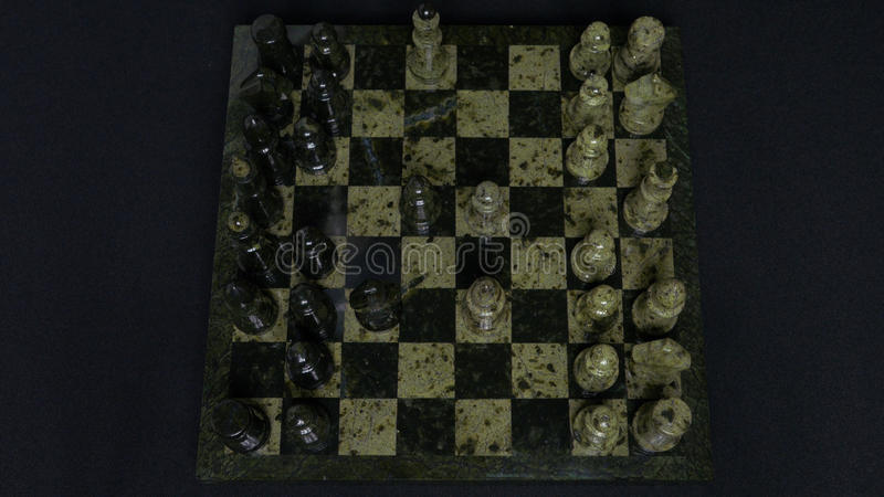 Checkmate. Start Of A Chess Game,the Figures Are Lined Up And A Person Makes The First Move. Hand moving a knight chess. Piece on chessboard. Man`s hands play stock images