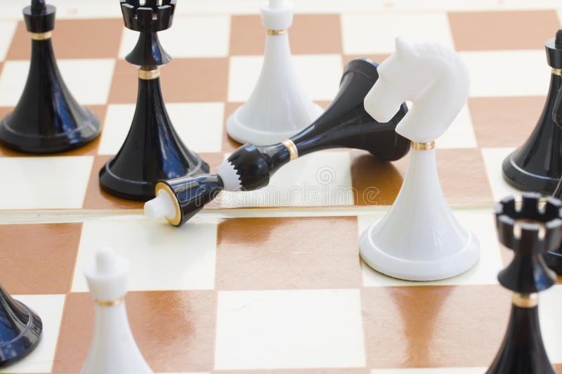 Checkmate white defeats black king. Checkmate white knight defeats black king close up royalty free stock photos