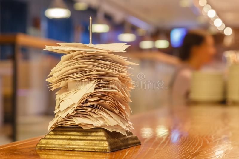 Checks from completed orders in the bar or restaurant kitchen impaled on a sharp thin iron needle on stand. Concept checker, stan. Checks from completed orders stock photos