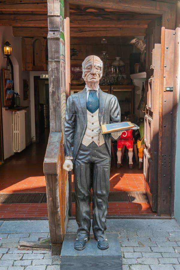 Checo Krumlov, República Checa 15 de agosto de 2017: a figura de madeira do garçom guarda o menu do café em sua mão, convidando v foto de stock royalty free