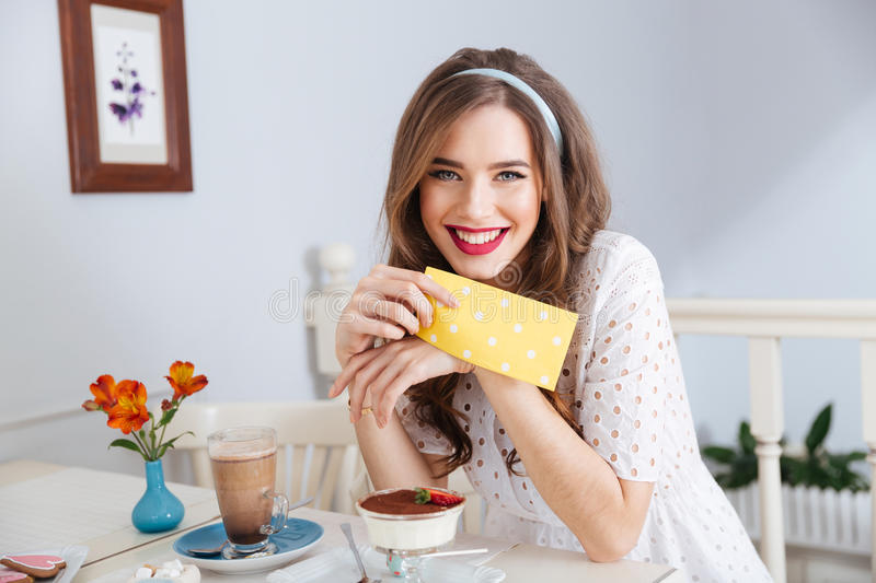Cheeerful attractive woman drinking latte and eating dessert in cafe. Cheeerful attractive young woman in white dress drinking latte and eating dessert in cafe royalty free stock photos