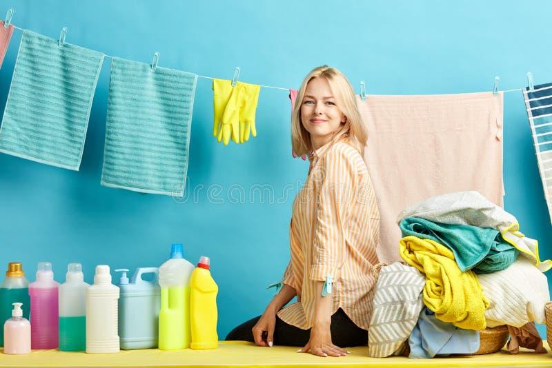 Cheeful女孩满意对完善的洗涤物的结果,广泛地使用优良品质洗涤剂,微笑 图库摄影