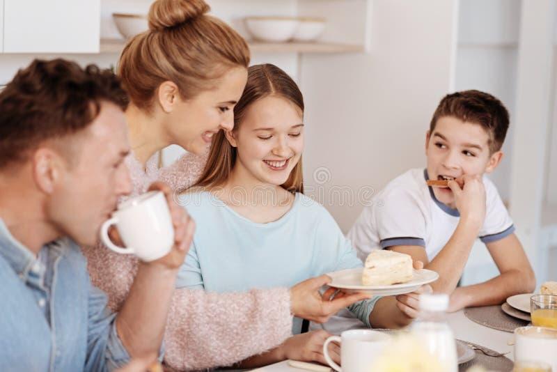 Cheeful家庭有膳食一起在厨房 免版税库存照片