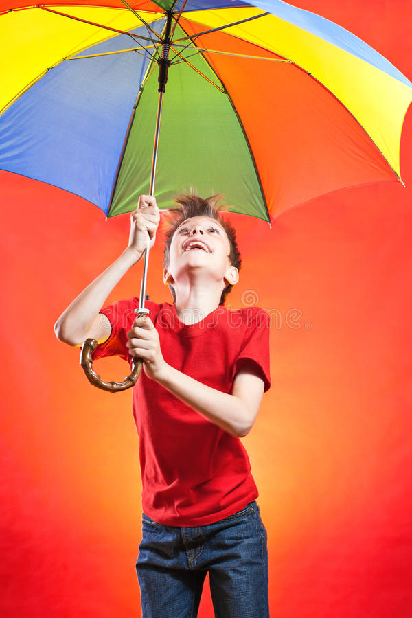 Cheeful funny boy in red t-shirt holding a multicolored umbrella stock image