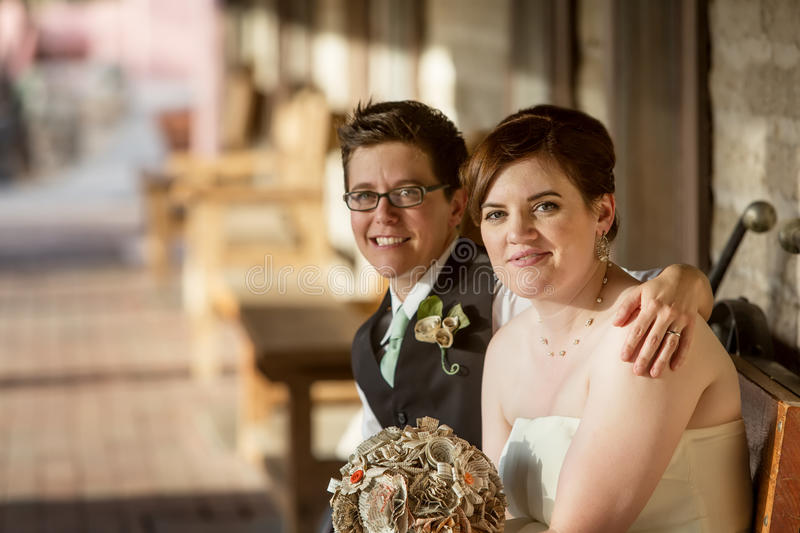 Cheeful Gay Couple. Cheerful Caucasian gay female couple sitting together stock image