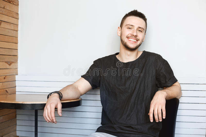 Cheefulkerel in zwarte t-shirtzitting bij heldere moderne ruimte royalty-vrije stock afbeelding