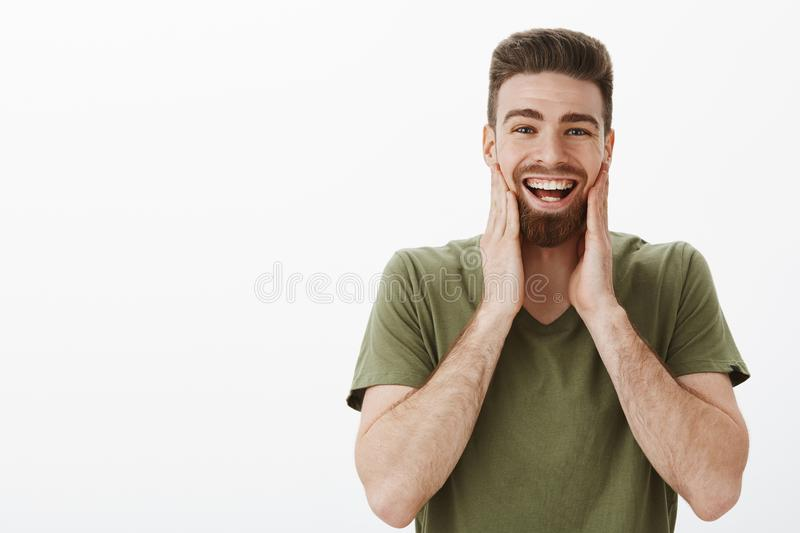 Cheeks hurt from laughing and smiling. Portrait of amused happy upbeat attractive bearded adult male in olive t-shirt royalty free stock image