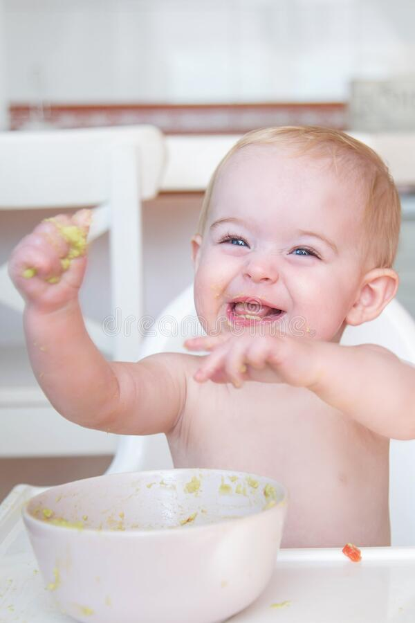 cheeky baby playing with food stock photos
