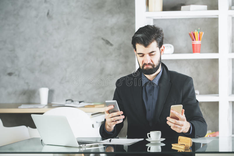 Cheeky businessman using two smartphones. Young businessman with cheeky face expression using two smartphones at workplace with laptop, coffee cup and supplies stock photos