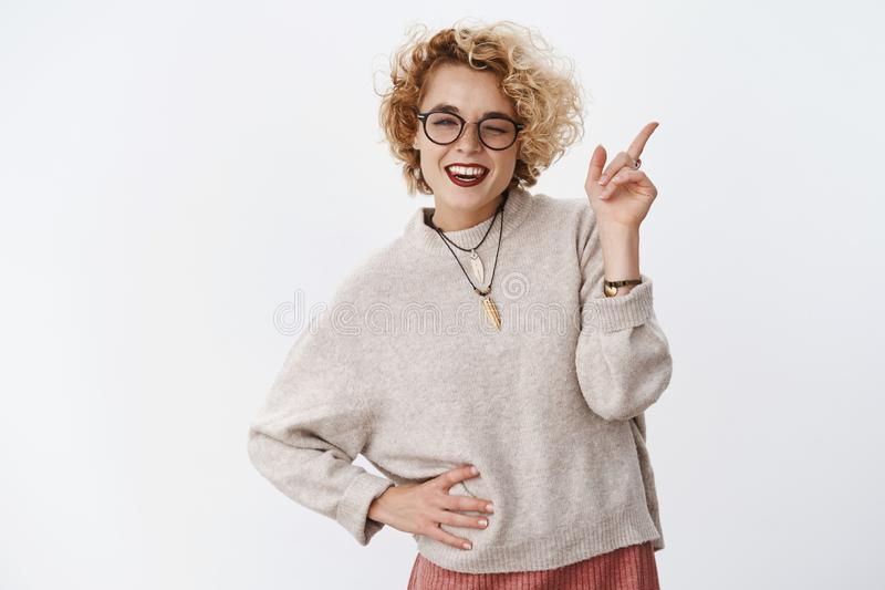 Cheeky and flirty cute pretty blond hipster female with charismatic smile winking joyfully, smiling and pointing at. Upper right corner as hinting at awesome royalty free stock photo