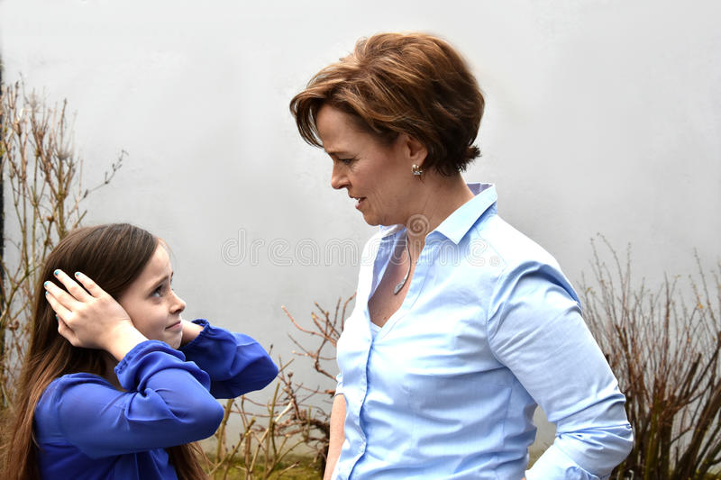 Cheeky girl with nerved mother stock image