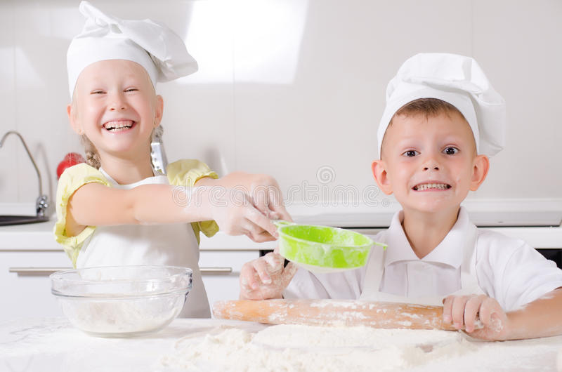 Cheeky happy little boy and girl in the kitchen royalty free stock photo