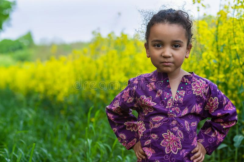 Cheeky Mixed Race African American Girl Child in Field of Yellow Flowers. Beautiful happy cheeky mixed race female African American girl child standing hands on royalty free stock images