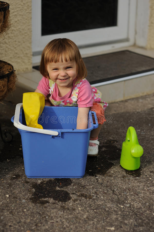 Cheeky Smile. A little girl playing with a blue bucket stock image