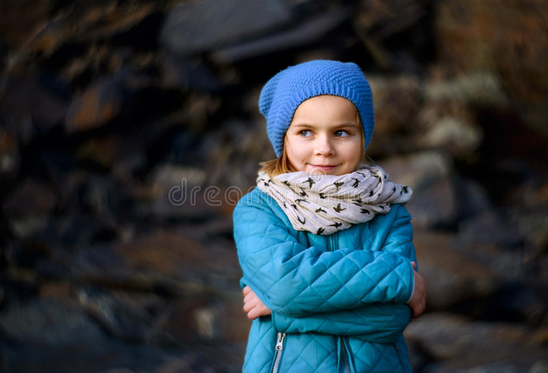 Cheeky Smile. A young girl smiling in blue stock image