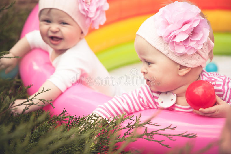 Cheerful сute babies twins playing outdoors in the garden royalty free stock image
