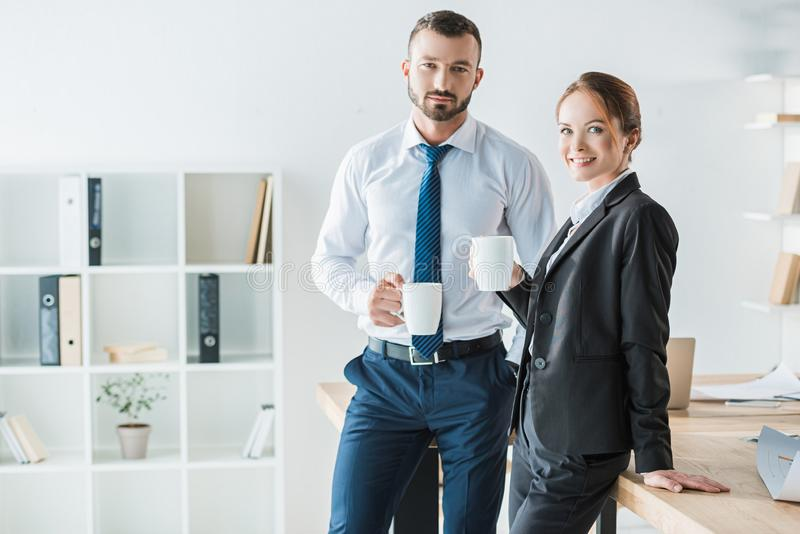 Cheerful accountants holding cups with coffee and looking at camera. In office royalty free stock images