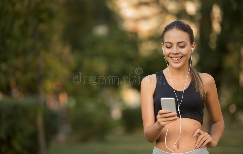 Cheerful active sporty girl choosing music for training stock photography