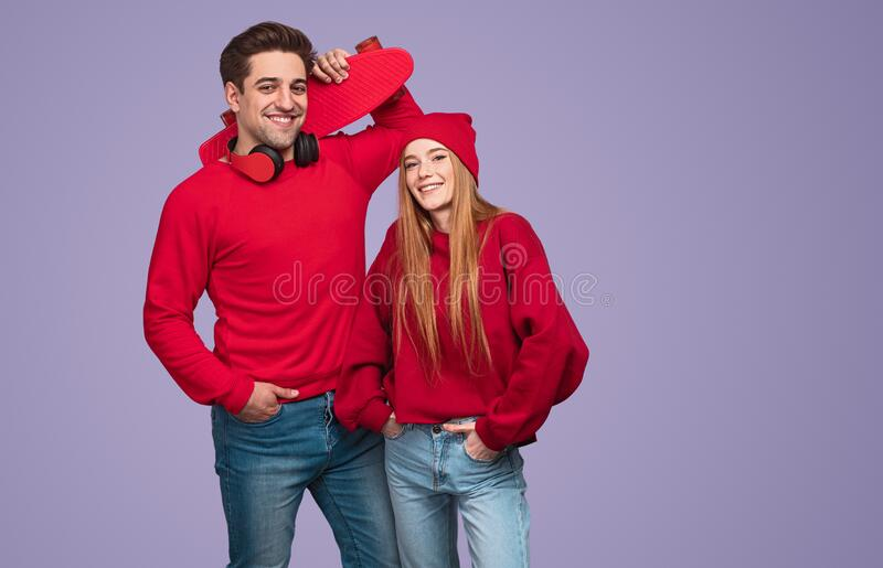 Cheerful active young couple with skateboard looking at camera royalty free stock photos