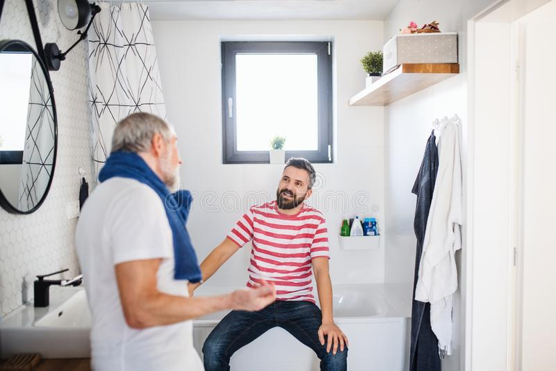 An adult hipster son and senior father in bathroom indoors at home, talking. royalty free stock photo