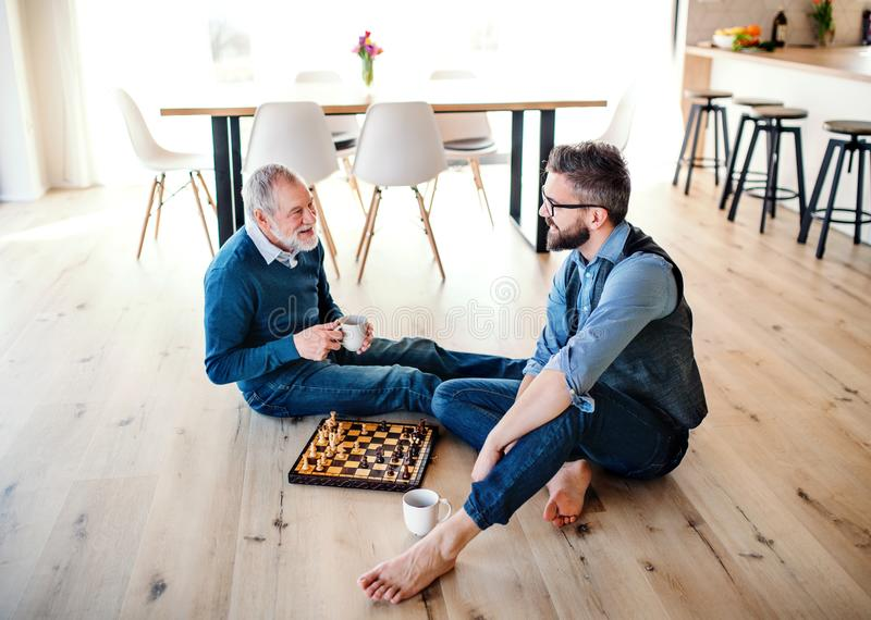 An adult hipster son and senior father sitting on floor indoors at home, playing chess. royalty free stock images